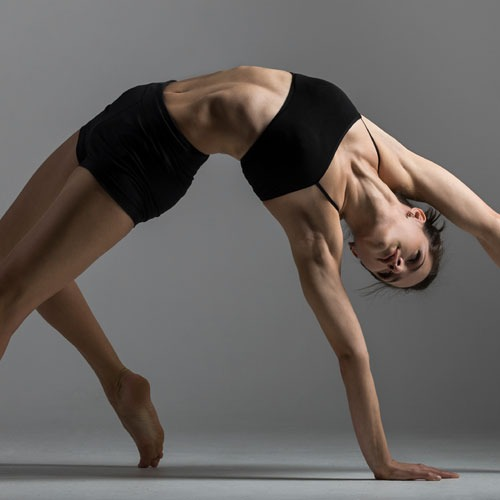 Blended classes with a woman bending backwards in a flexible yet fit yoga pose